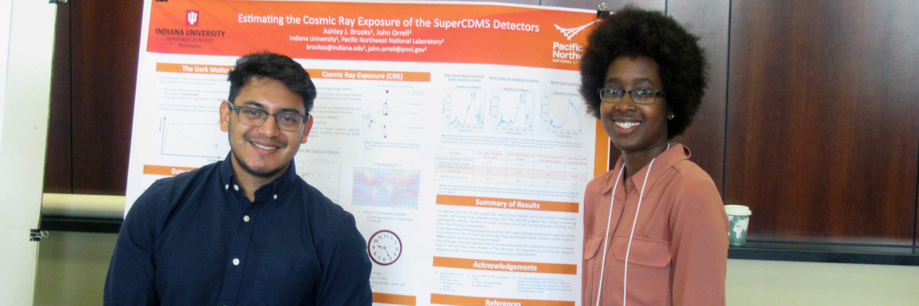 Two Bridge program students in front of a presentation board