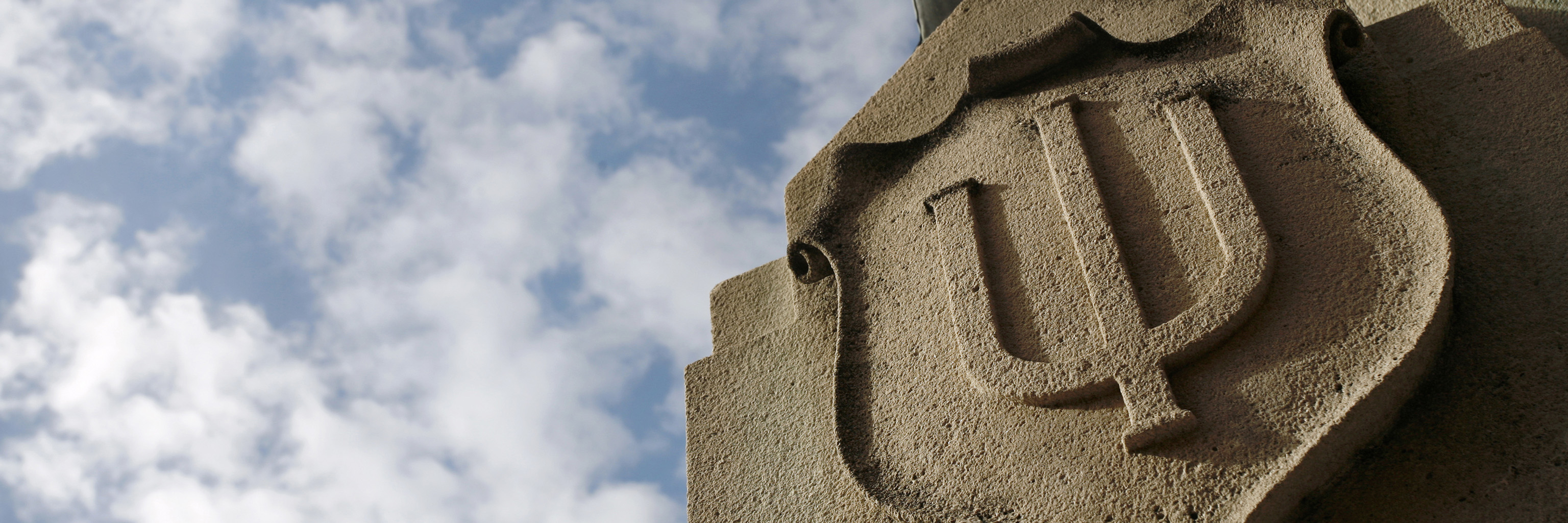 Limestone relief of a crest decorated with the Indiana University trident
