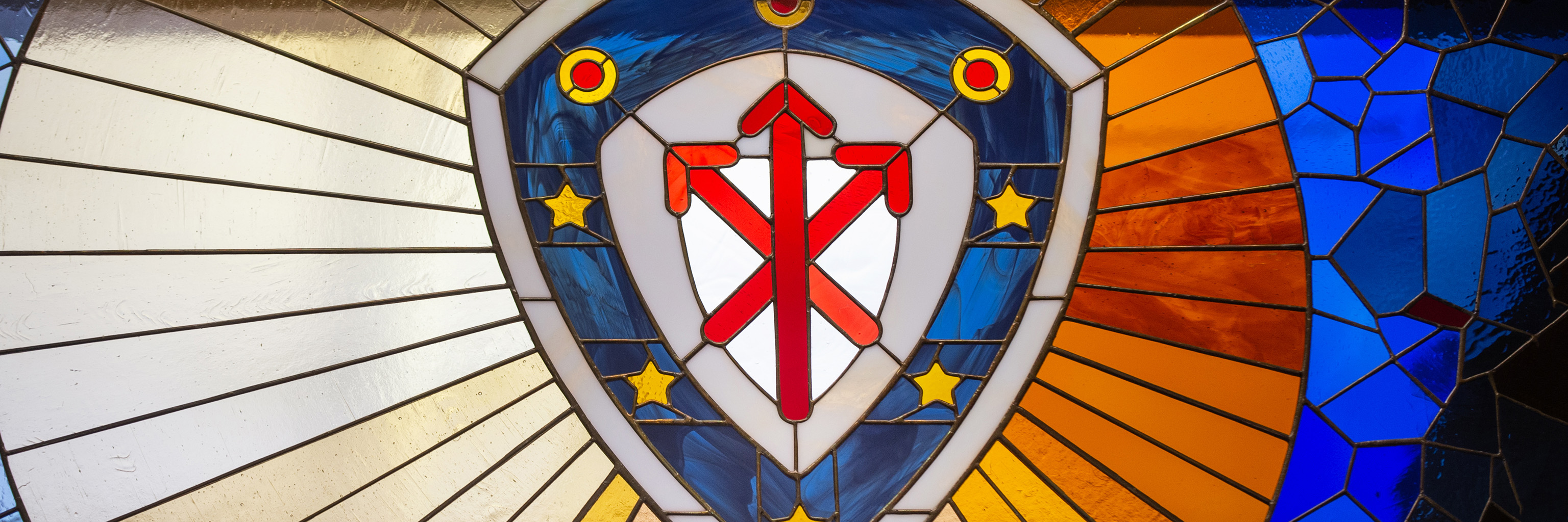 The Indiana University College of Arts and Sciences shield design displayed in stained glass