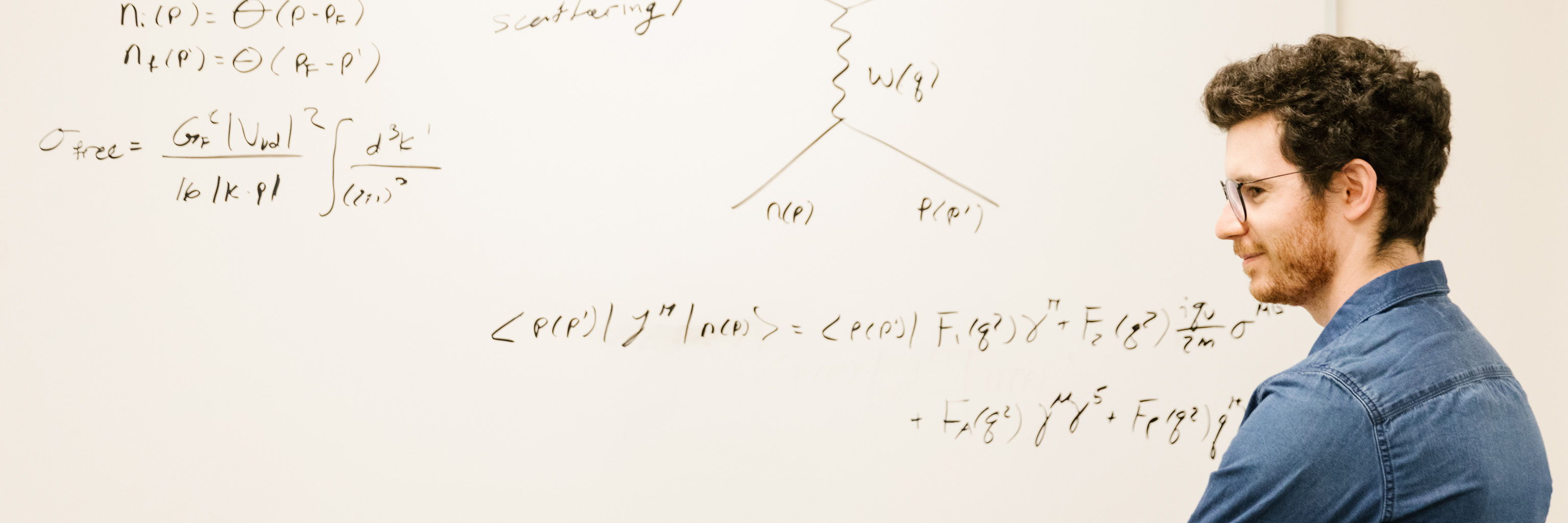 Man standing in front of a white board covered in equations