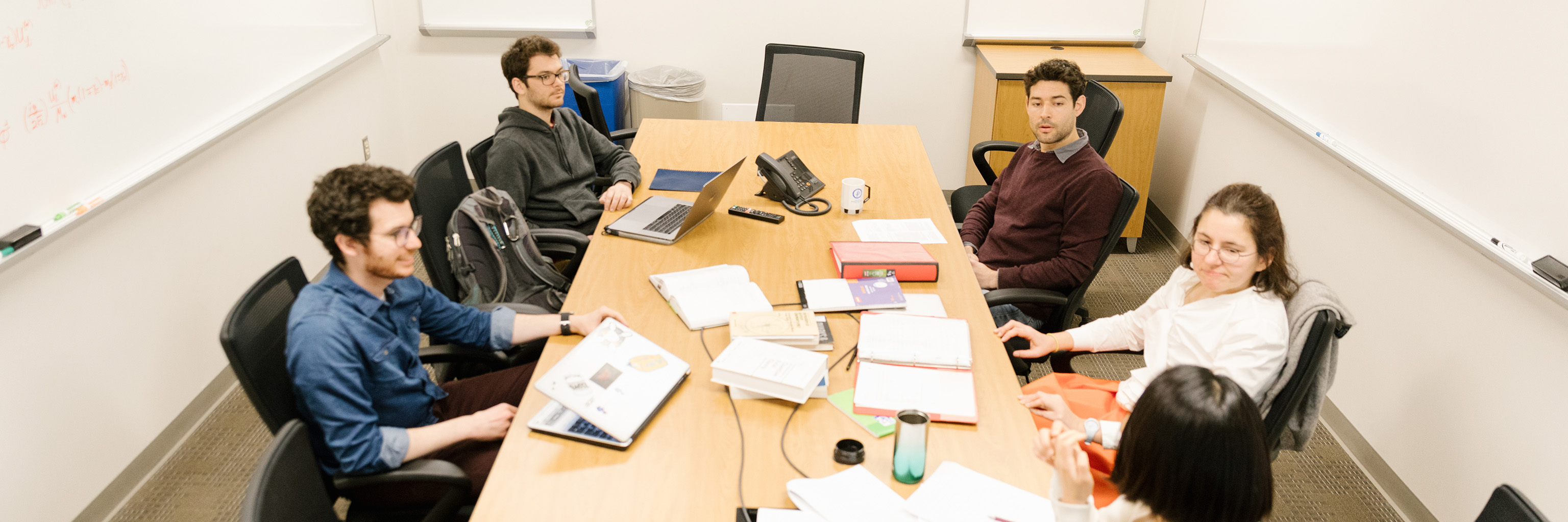 Graduate students convened around a conference table