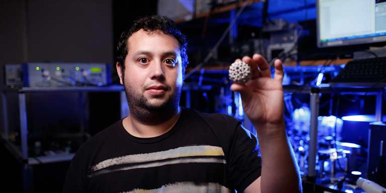 A man holding up a small model of a particle