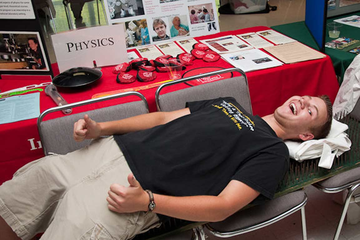Student participating in a demonstration in front of a table for the physics department