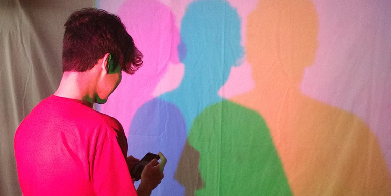 A man looking at his shadow, which has been split into pink, blue, and yellow overlapping shadows.