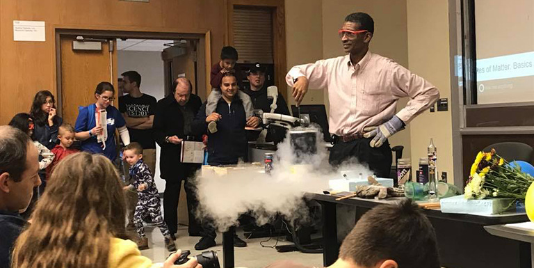 A professor performing a physics demonstration with dry ice for a group of school-age children.