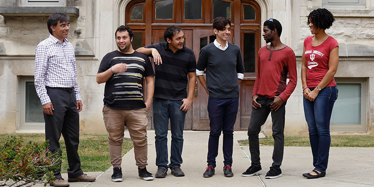 Five students and a professor laughing and talking to one another outside of a classroom building.